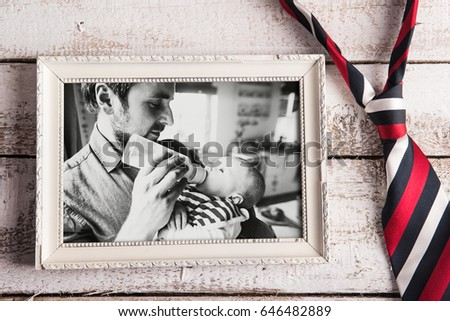 Picture of father feeding baby son. Fathers day. Studio shot.