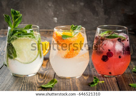 Selection of three kinds of gin tonic: with blackberries, with orange, with lime and mint leaves. In glasses on a rustic wooden background. Copy space #646521310