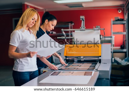 Two young woman working in printing factory. Printing Press #646615189