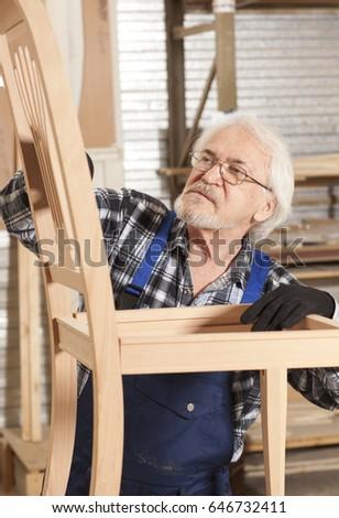 Senior carpenter working in furniture factory #646732411