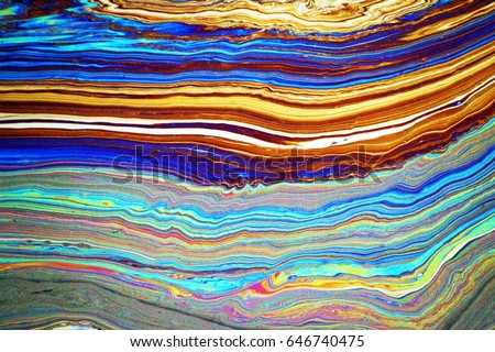a photo of rainbow colored oil floating on water. natural.
