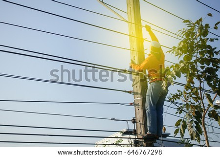 Electrician lineman working repair a wire system on an electric pole #646767298