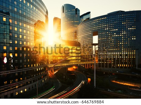Modern buildings in Paris business district La Defense. Glass facade skyscrapers on a bright sunny day with sunbeams in the blue sky. Economy, finances, business activity and city traffic concept #646769884