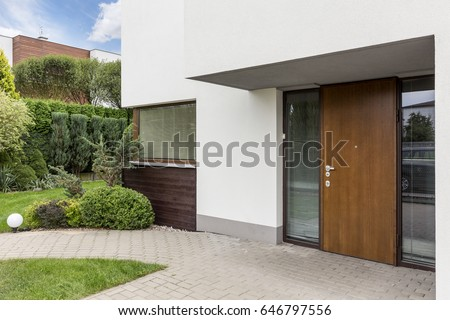 Wooden entrance door to modern white house with paving footpath and backside garden Royalty-Free Stock Photo #646797556