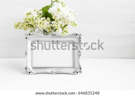Vintage silver photo frame with lilac flowers on white still life board