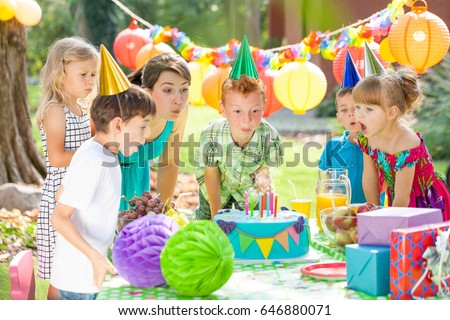 Group of children and animator blowing off he candles from the cake #646880071