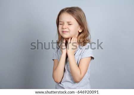 Little ill girl with sore throat on color background. Concept of allergy Royalty-Free Stock Photo #646920091