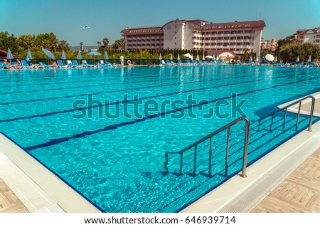 Alanya, Turkey - May, 5, 2017: Big Olympic swimming pool in the open air. Ripples on the surface of turquoise water. Sun loungers and umbrellas around the pool, people sunbathe and swim. #646939714