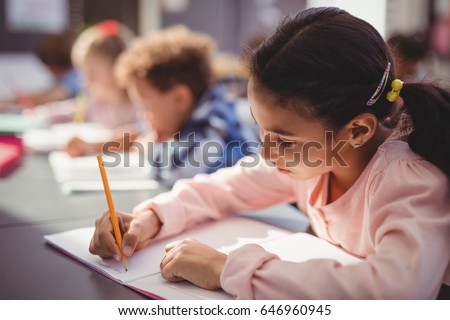 Close up of attentive schoolgirl doing her homework in classroom at school #646960945