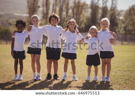 Portrait of happy schoolgirls standing with arms around in park on a sunny day #646975513