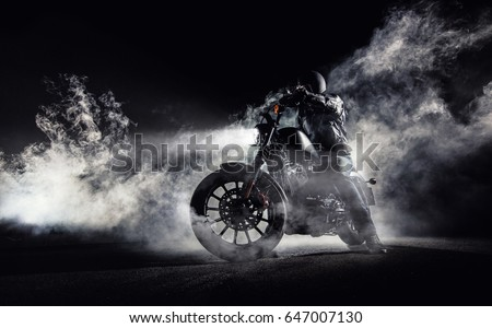 High power motorcycle chopper with man rider at night. Fog with backlights on background. #647007130