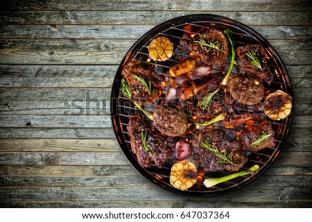 Top view of fresh beef steaks, chicken legs, sausage and vegetable on grill placed on wooden floor. Barbecue, grill and food concept #647037364