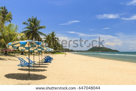 Beach Chairs With Umbrellas On The White Sand Beach With Cloudy Blue Sky. #647048044