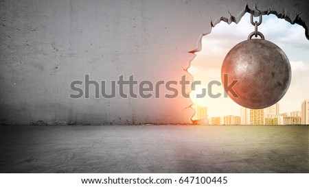 A black wrecking ball hanging inside the opening in a concrete wall showing city landscape. Old building demolition. New construction site. Freshen up your life. Royalty-Free Stock Photo #647100445