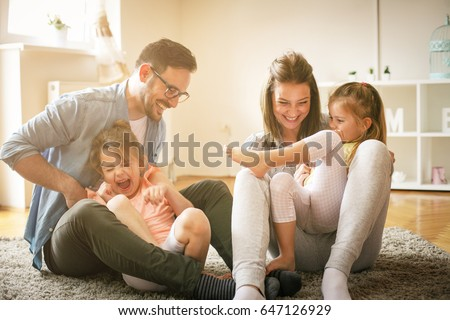Happy family with two daughters playing at home. Family sitting on floor and playing together. #647126929