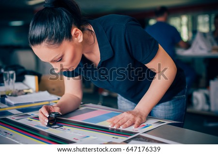Worker in a printing and press centar uses a magnifying glass and check the print quality #647176339