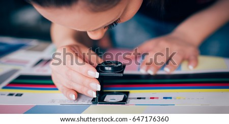 Worker in a printing and press centar uses a magnifying glass and check the print quality #647176360