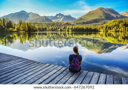 Girl sitting by the lake under mountains- nature photo with copy space. Strbske pleso, Slovakia.