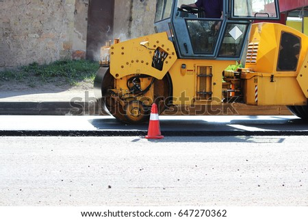 Powerful compactor compacts and levels the soil in front of the road asphalting. #647270362