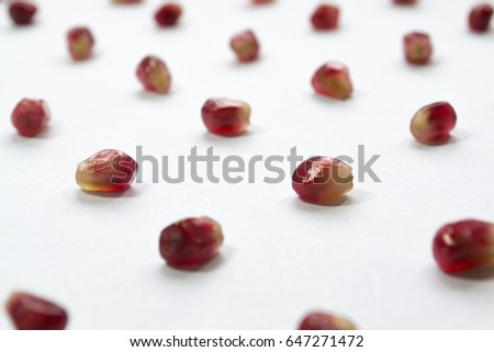 Red pomegranate seeds isolated on white background. Polka dots pattern. #647271472