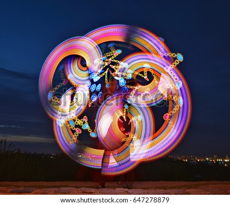 Pixel poi in motion on the dark sky. Bright openwork waves of colored light against the background of the evening sky. Abstract multicolored light on a dark background