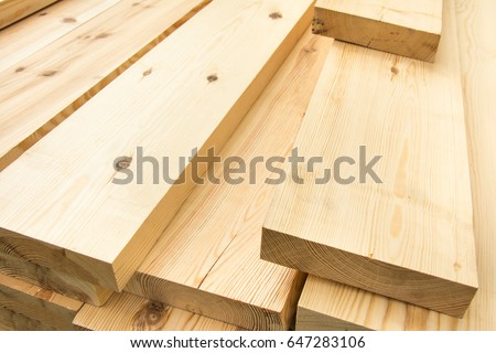 Piled lumber near a lumber mill, waiting for shipping. Wood Mill. Lumber and wood slice. #647283106