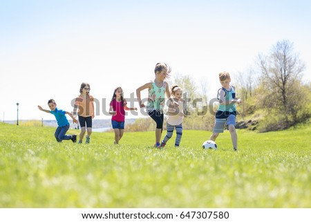 Boys and girls running towards ball on a field #647307580