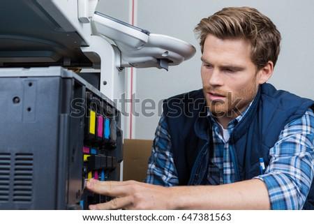 Man servicing photocopier #647381563