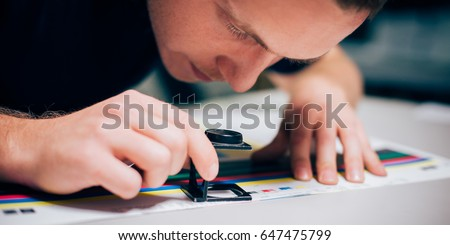 Worker in a printing and press centar uses a magnifying glass and check the print quality #647475799