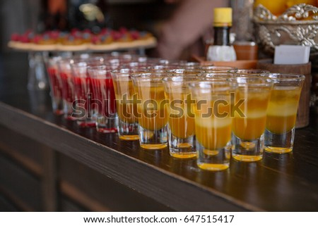 Shot glasses on the bar table. Yellow and red cocktails on a buffet table #647515417
