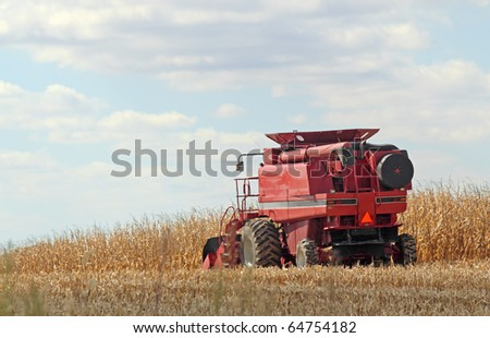 Red combine harvesting a farm field of corn #64754182