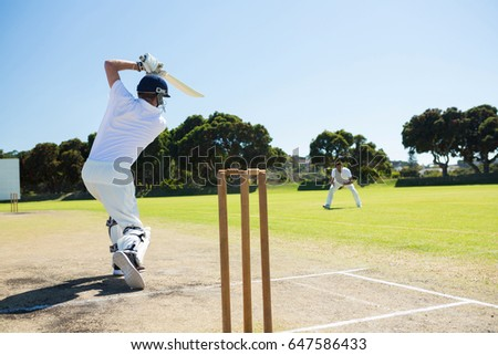 Rear view of player batting while playing cricket on field against clear sky