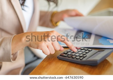 The right hand woman manager is pressing the calculator. And look at the graph file on the desk. #647630590