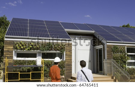 Solar construction workers looking at the roof.  Plants are from a gray water recovery system. #64765411