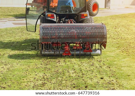 Gardener Operating Soil Aeration Machine on Grass Lawn #647739316