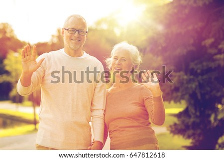 family, age, tourism, gesture and people concept - senior couple waving hands in city park #647812618