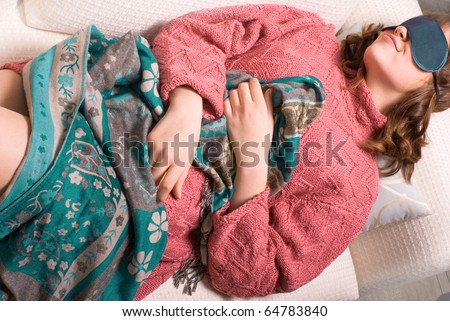 Portrait of Young Attractive Woman Sleeping with Mask on Sofa Wearing Warm  Sweater #64783840