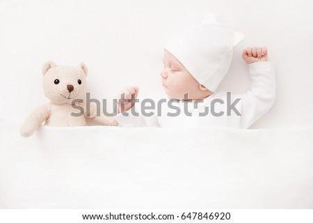 New born Baby girl sleeping with her teddy bear Royalty-Free Stock Photo #647846920