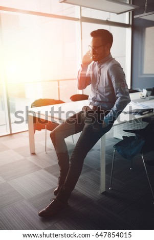 Handsome businessman in contemporary office building #647854015