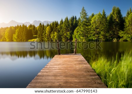Idyllic view of the wooden pier in the lake with mountain scenery background. Alps in the early morning. Royalty-Free Stock Photo #647990143