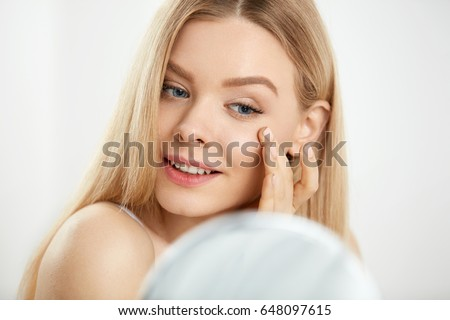 Makeup And Beauty Care. Closeup Beautiful Sexy Woman With Fresh Natural Makeup And Healthy Soft Smooth Skin Touching Face And Looking In Mirror. Young Female Massaging Skin Under Eyes. High Resolution #648097615