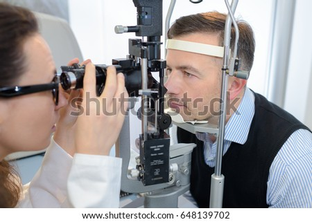 young female ophthalmologist and male patient checking eyesight #648139702