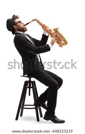 Jazz musician seated on a chair playing a saxophone isolated on white background #648223219