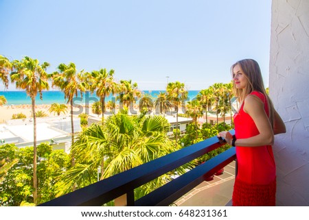 Beautiful girl in a red dress standing on the Palm Beach hotel balcony with a view on the Atlantic ocean and palms in front of it. #648231361