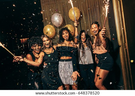Shot of group of girls in the nightclub having a great time. Group of female friends partying in pub. #648378520