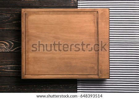Rectangular cutting board on wooden table #648393514