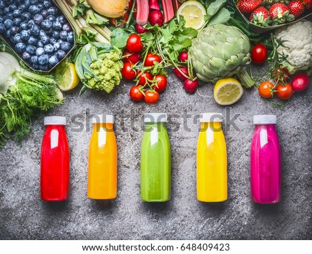 Healthy red, orange, green, yellow and pink Smoothies  and juices in Bottles on grey concrete background with fresh organic vegetables , fruits and berries ingredients, top view #648409423