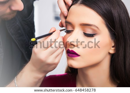 Male in the black hat make-up artist Draws arrows on the eyelids to brunette girl in beauty salon, close-up #648458278