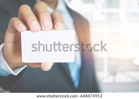 Young business man wear suit holding white business card on modern office blur background. #648474952