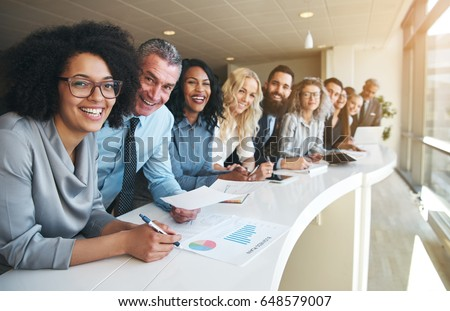 Smiling black and white coworkers looking at camera in the office. Royalty-Free Stock Photo #648579007